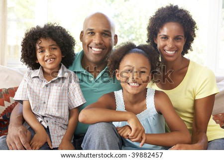 Young Family Relaxing On Sofa At Home - stock photo