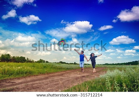 Young family running in a field with a kite - stock photo