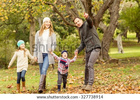 Young family running in leaves on an autumns day - stock photo