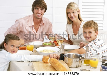 Young family seated at the table enjoying their meal of spaghetti bolognaise and salads