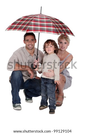 Young family sheltering under an umbrella