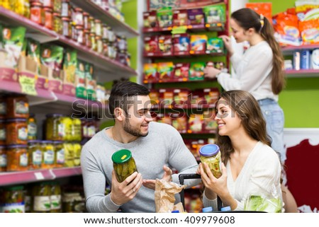 Young family shopping food for week at supermarket - stock photo