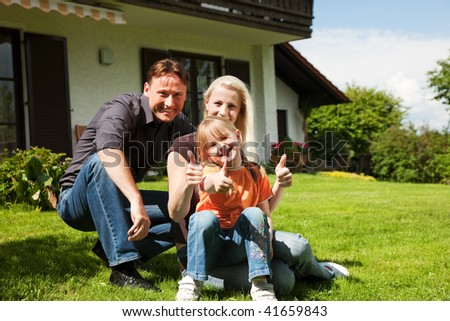 Young family sitting in the sun on the lawn in front of their new home - a single house