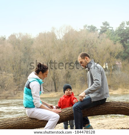 Young family sitting on a tree near the river