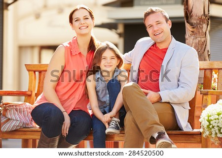 Young Family Sitting On Seat In Mall Together - stock photo