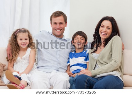 Young family sitting on the couch together - stock photo