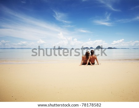 Young family sitting on warm sand by a sea and looking to somewhere - stock photo