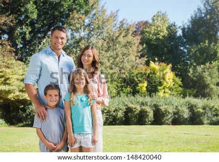Young family standing in a park and smiling at a camera - stock photo