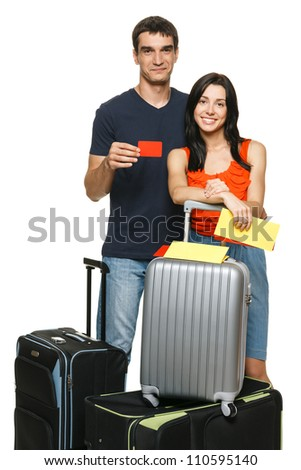Young family standing with suitcases holding empty credit card, over white background. Travel credit card.