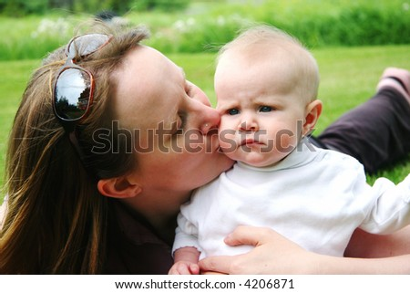 Young family together in grass - mother and baby - stock photo