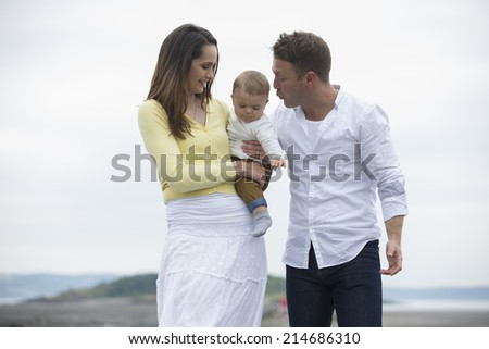 Young Family together on beach. Mum, dad and baby boy on winter beach.