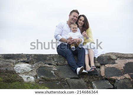 Young Family together on beach. Mum, dad and baby boy on winter beach. - stock photo