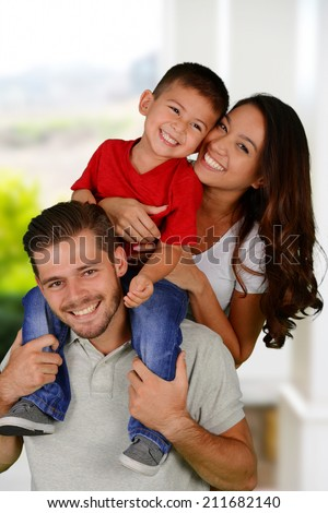 Young family together outside of their home - stock photo