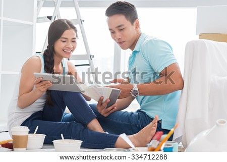Young family trying to find perfect color for their room - stock photo