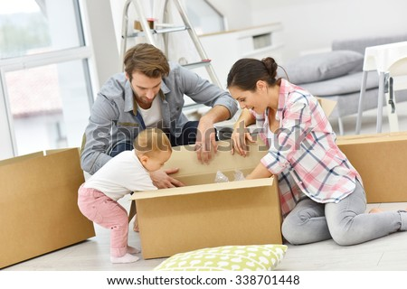 Young family unpacking boxes in new home - stock photo