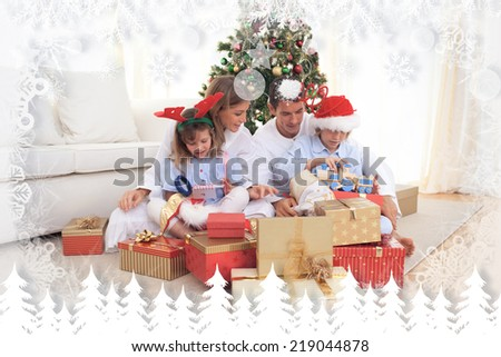 Young family unpacking Christmas presents against fir tree forest and snowflakes - stock photo
