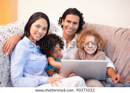 Young family using laptop on the sofa together - stock photo