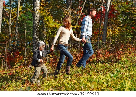 young family walking in the fall forest