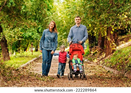 Young family walking in the park. Autumn.