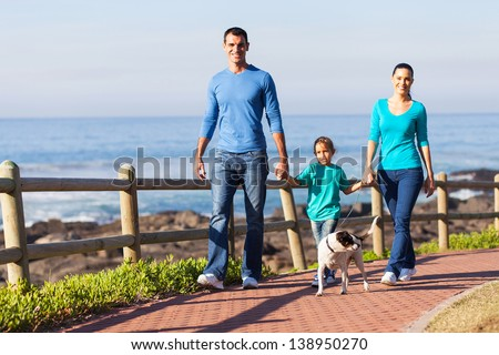 young family walking their dog at the beach - stock photo