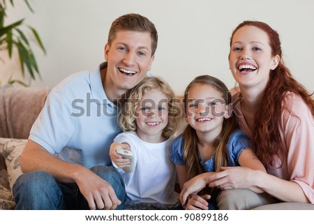 Young family watching a funny movie - stock photo