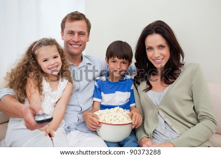 Young family watching a movie together - stock photo