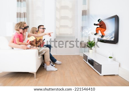 Young Family Watching 3D TV At Home - stock photo