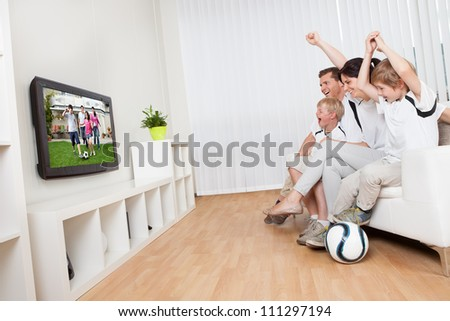 Young family watching football match at home - stock photo