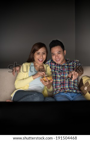 Young family watching funny program on tv - stock photo