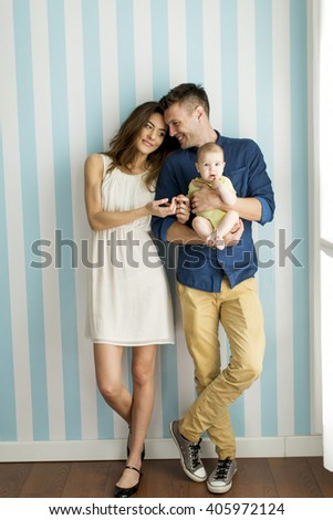 Young family with a baby standing by the wall - stock photo