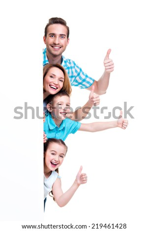 Young family with a banner showing the thumbs-up sign - isolated on a white background - stock photo