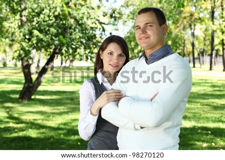 Young family with a child in green summer park - stock photo
