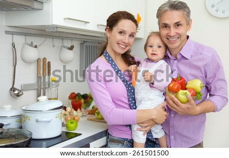 young family with a child in the kitchen at home - stock photo