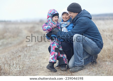 young family with a child playing on winter field - stock photo