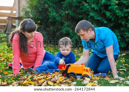 Young family with a child walks in autumn park. - stock photo