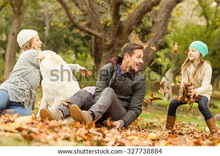 Young family with a dog in leaves on an autumns day - stock photo