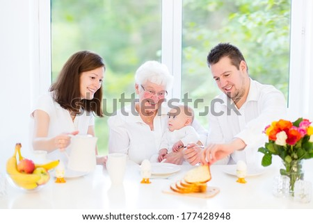 Young family with a little baby having breakfast with their loving grandmother in a beautiful white dining room with a big garden view window - stock photo
