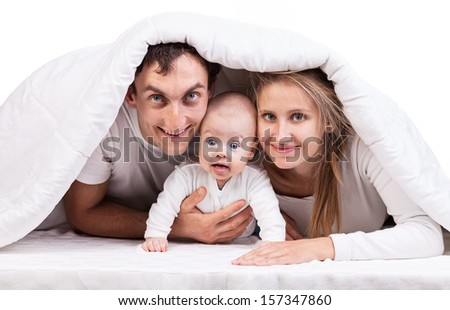 Young family with baby boy under blanket on bed at home