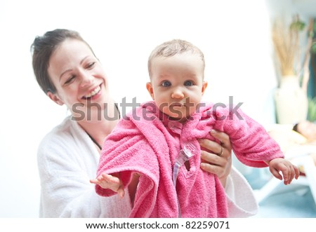 Young family with baby having fun in the swimming pool.