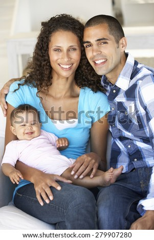 Young Family With Baby Relaxing On Sofa At Home - stock photo