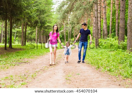 young family with child walks in the park.