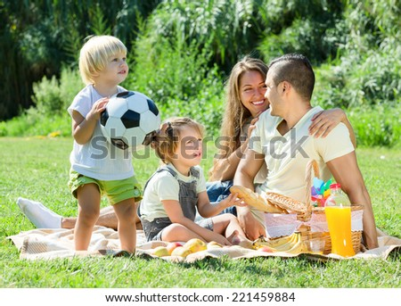 Young family with children having picnic outdoor on sunny day - stock photo