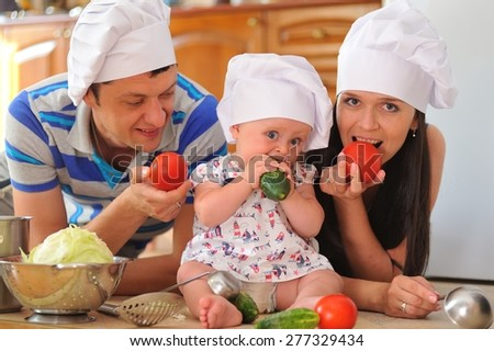 Young family with cooking hoods on their heads: a little cute baby-girl is sitting on the kitchen floor, she is eating cucumber - her parents are lying next to her, eating tomato and playing cooks - stock photo