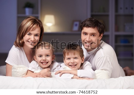 Young family with kids at night in the bedroom - stock photo