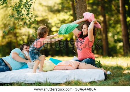 Young family with kids having fun with colored pillows outdoors. Parents with two children relax in a sunny summer garden. Mother, father, little girl and baby boy playing in park. Pillow fight - stock photo
