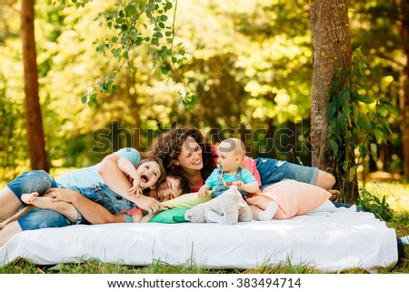 Young family with kids having picnic with colored pillows outdoors. Parents with two children relax in a sunny summer garden. Mother, father, little girl and baby boy playing in park. - stock photo