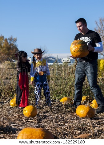 Young family with kids in costumes looking for big pumpkin on pumpkin patch. - stock photo