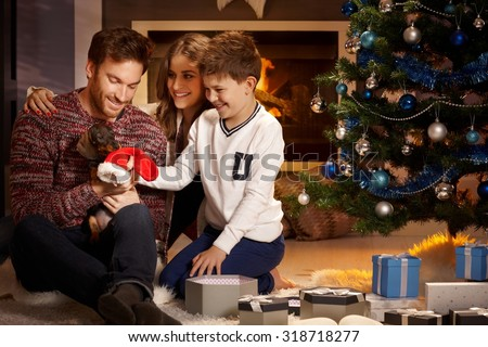 Young family with little boy holding puppy received for christmas.