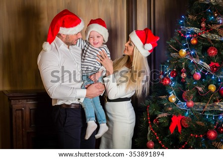 Young family with  little son stand near Christmas tree in the room. Merry Christmas and Happy New Year. - stock photo