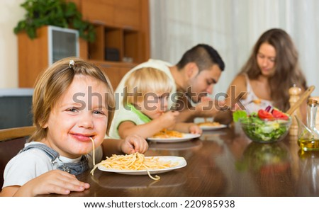 Young family with playful kids eating with spaghetti at table. Focus on girl  - stock photo